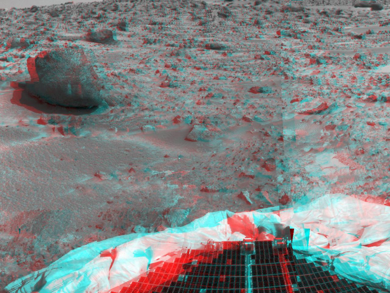 This image from NASA's Mars Pathfinder shows the large rock nicknamed 'Yogi.' Portions of a petal and deflated airbag are in the foreground. 3-D glasses are necessary to identify surface detail.
