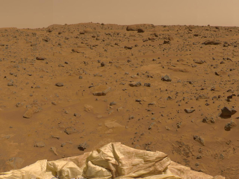 This view to the Northeast was imaged by NASA's Imager for Mars Pathfinder (IMP) as part of a 360-degree color panorama, taken over sols Jul. 12-14, 1997. A deflated airbag is at the bottom of the image.