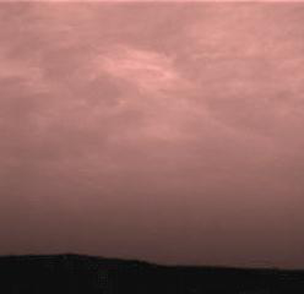 Pink stratus clouds are coming from the northeast at about 15 miles per hour at an approximate height of ten miles above the surface. The image was taken by NASA's Imager for Mars Pathfinder (IMP) on Sol 16. Sol 1 began on July 4, 1997.