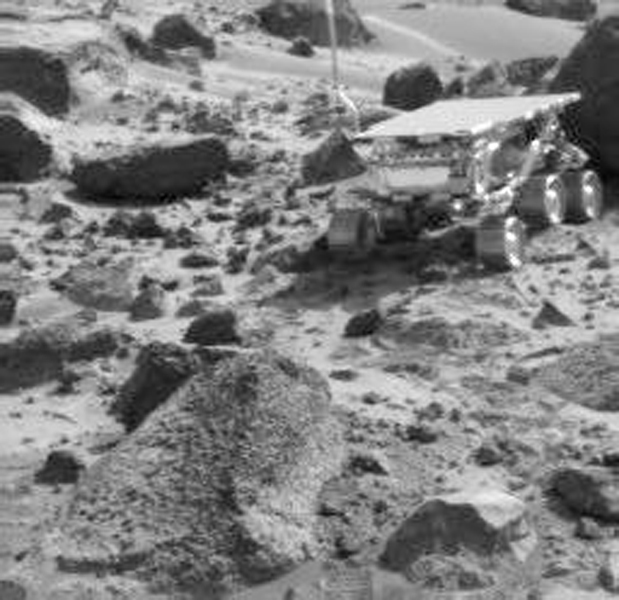 NASA's Imager for Mars Pathfinder (IMP) image taken near the end of daytime operations on Sol 50 shows the Sojourner rover between the rocks 'Wedge' (foreground) and 'Shark' (behind rover). Sol 1 began on July 4, 1997.