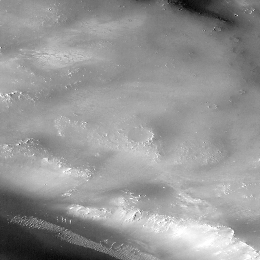 Small depressions found in the upper left and center of image with faint dark lines crossing lighter floors as seen by NASA's Mars Global Surveyor in 1997.