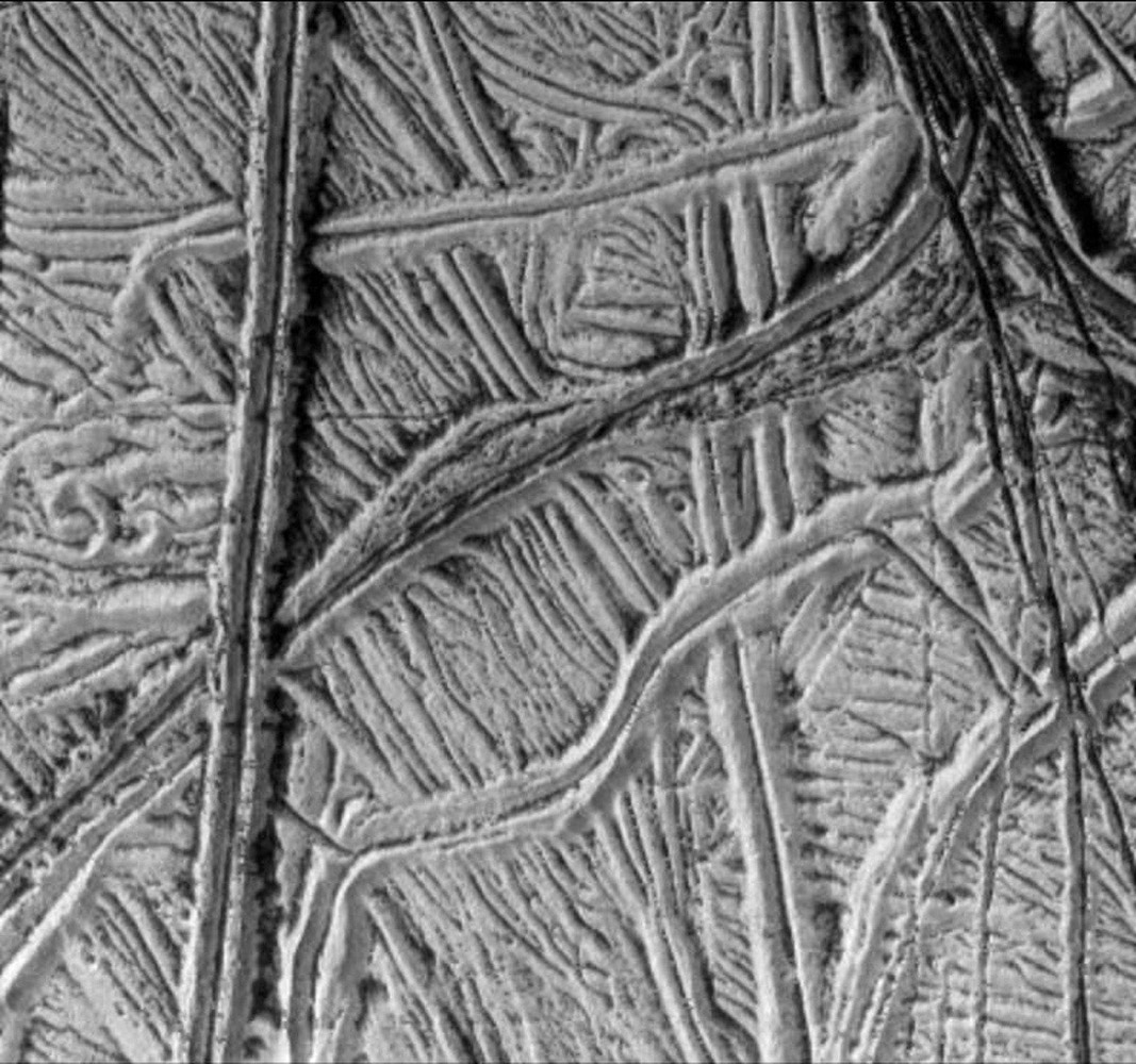 This spectacular image taken by NASA's Galileo spacecraft camera shows a region of ridged plains on Jupiter's moon Europa. The plains are comprised of many parallel and cross-cutting ridges, commonly in pairs.