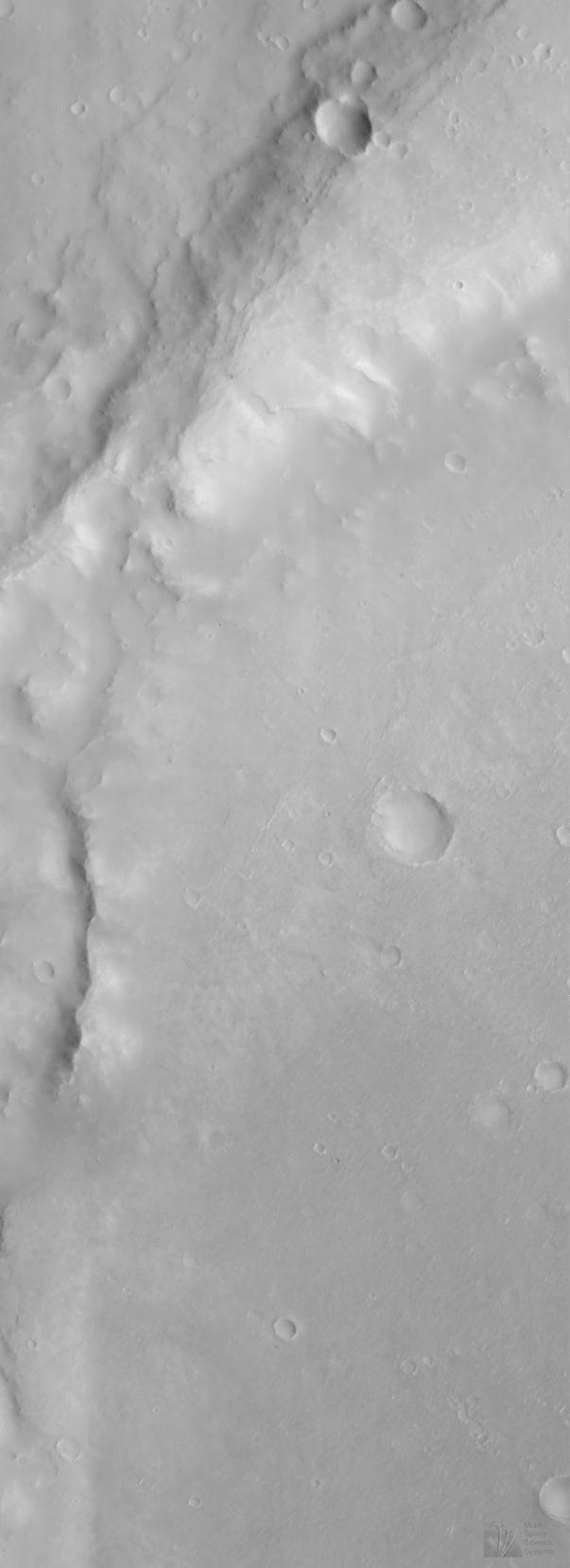 NASA's Mars Global Surveyor acquired this image on June 10, 1998. Shown here is an eroded portion of the thick ejecta (material thrown out of an impact crater during its formation) from a very large impact basin, Huygens.