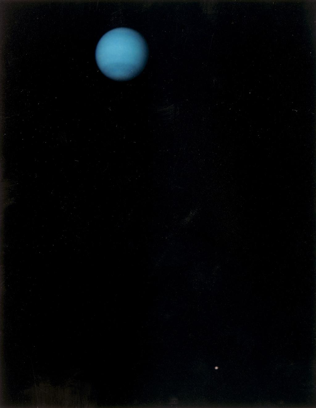 This image was returned by NASA's Voyager 2 spacecraft on July 3, 1989. The planet and its largest satellite, Triton, are captured in view; Triton appears in the lower right corner at about 5 o'clock relative to Neptune.