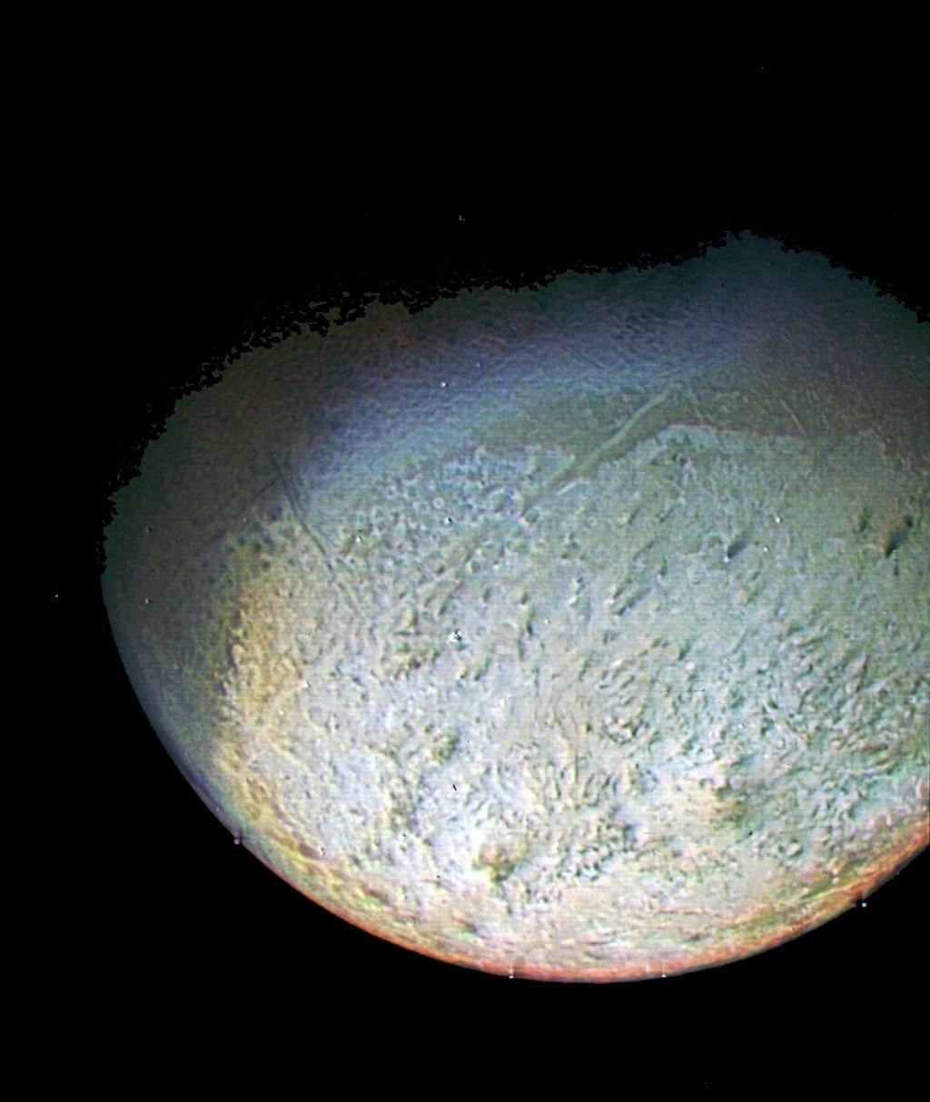 This color photo of Neptune's large satellite Triton was obtained on Aug. 24 1989. In reality, there is no part of Triton that would appear blue to the eye. The bright southern hemisphere of Triton, which fills most of this frame, is generally pink.