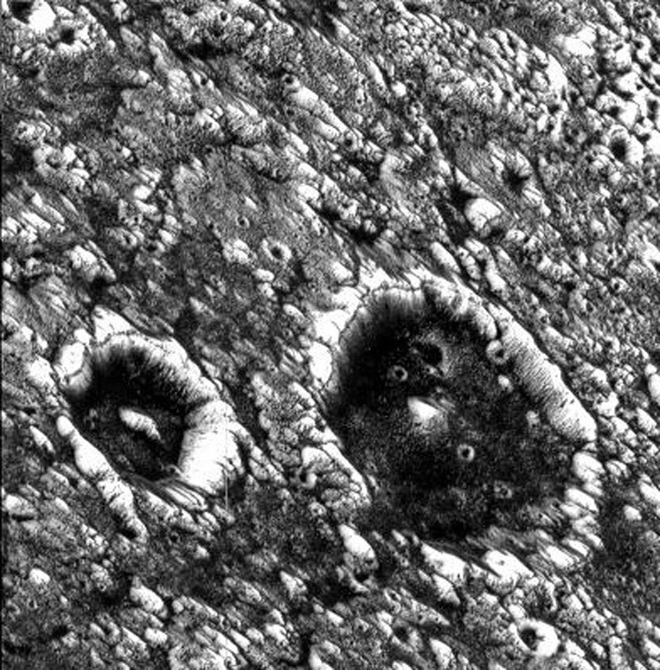 This image from NASA's Galileo spacecraft shows two impact craters that are superimposed on Memphis Facula, a large bright circular feature in the otherwise generally dark terrain in Galileo Regio on Jupiter's moon, Ganymede.