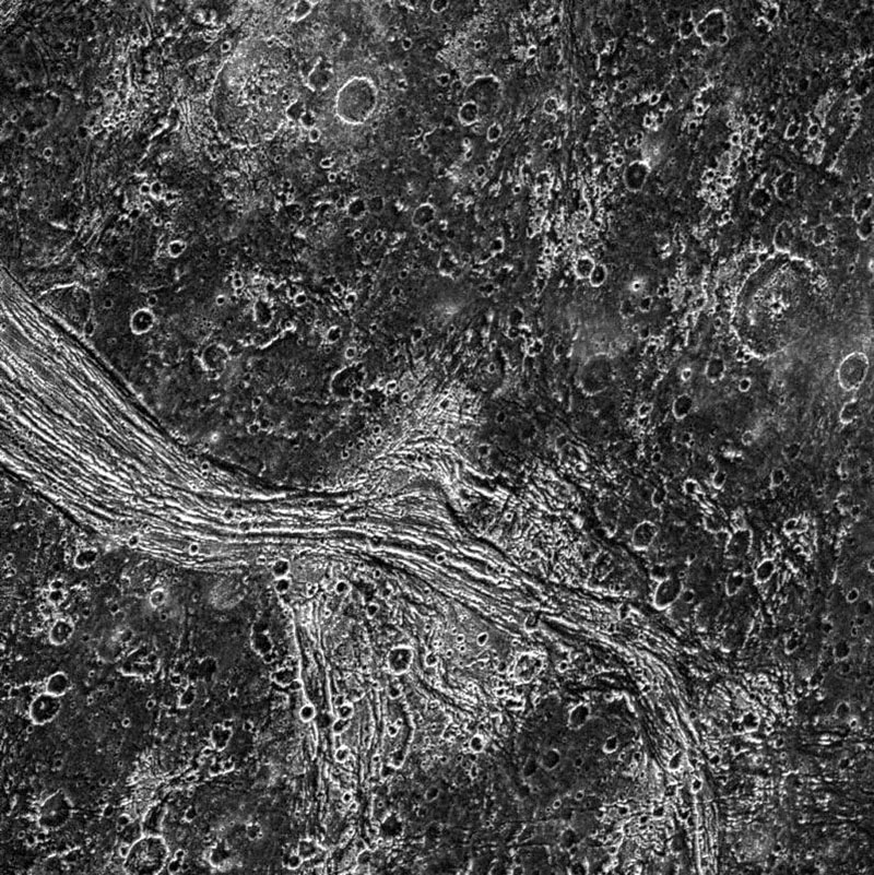 This image from NASA's Galileo spacecraft shows a highly fractured lane of grooved terrain, Lagash Sulcus, which runs through an area of heavily cratered dark terrain within Marius Regio on Jupiter's moon Ganymede.