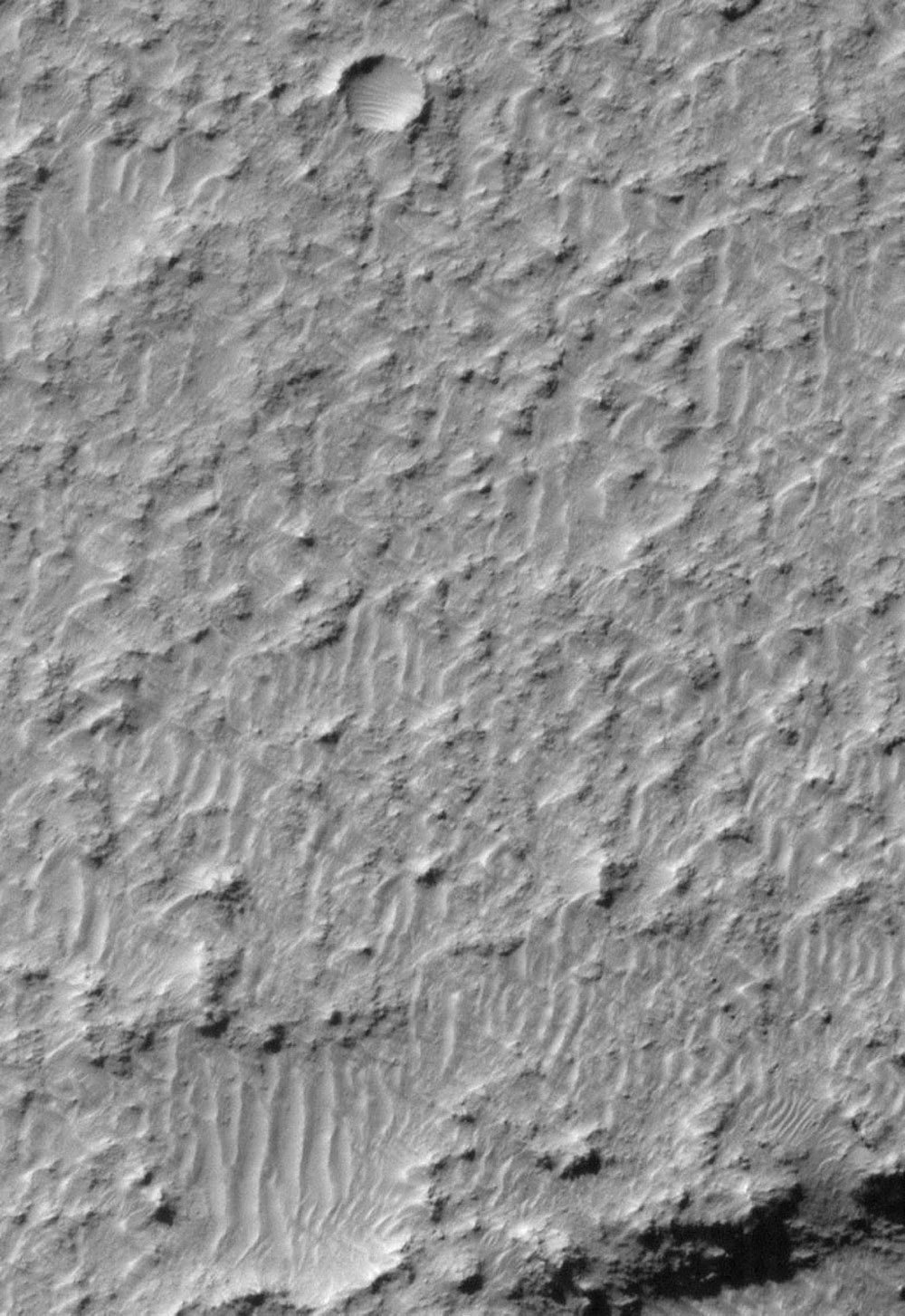 NASA's Mars Global Surveyor shows a view of a tiny portion of the southeastern floor of Mariner Crater pocked with craters.