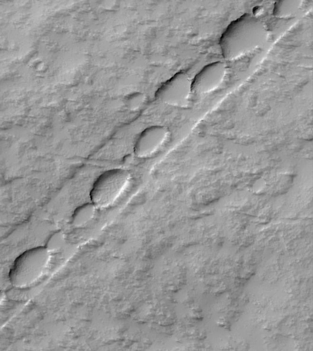 NASA's Mars Global Surveyor shows a chain of elliptical pits on the lower east flank of Pavonis Mons on Mars. The pits follow the trend of these faults, and indicate the locus of collapse.