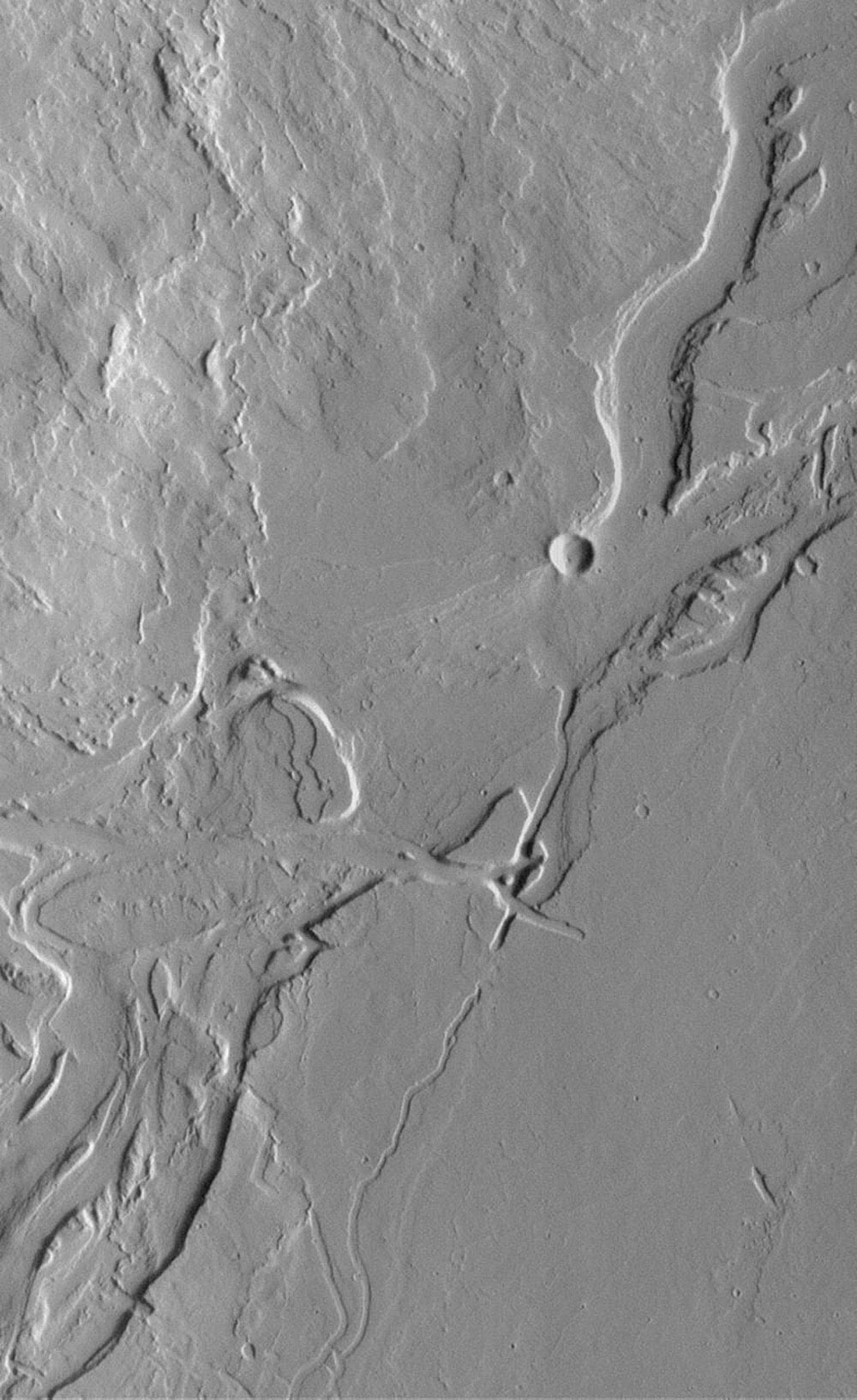 NASA's Mars Global Surveyor shows the volcanic Tharsis region, including these valleys and associated lava flows on the plains southeast of Olympus Mons. Lava flows are visible, but meandering valleys with streamlined 'islands' dominate the scene.