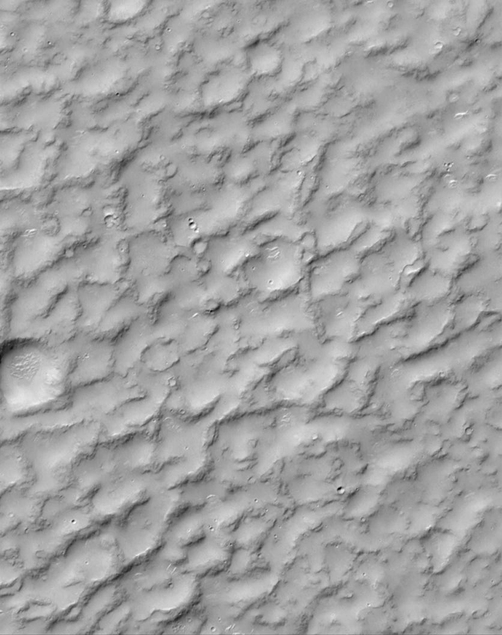 NASA's Mars Global Surveyor shows rounded, rocky ridges separated by lowlands filled with sand or dust in a complex, ridged terrain in North Terra Cimmeria on Mars.