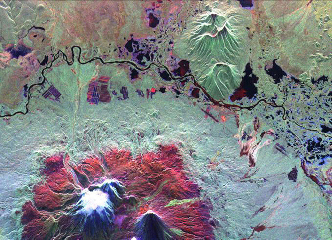 This is an image from NASA's Spaceborne Imaging Radar C/X-Band Synthetic Aperture Radar of the Kliuchevskoi volcano, Kamchatka, Russia, which erupted on September 30, 1994. Kliuchevskoi is the bright white peak surrounded by red slopes.
