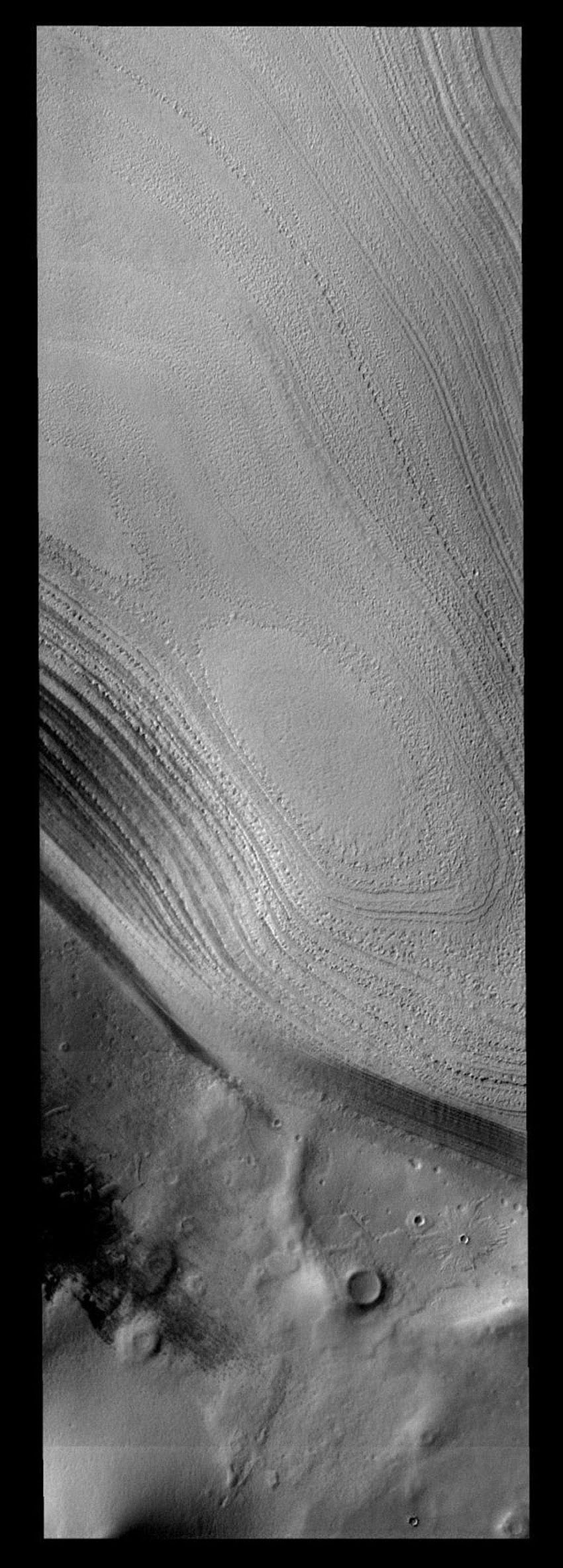 Taken during southern summer, this image from NASA's 2001 Mars Odyssey spacecraft shows both the ice layers of the southern polar cap of Mars and the dusty surface that surrounds the cap.