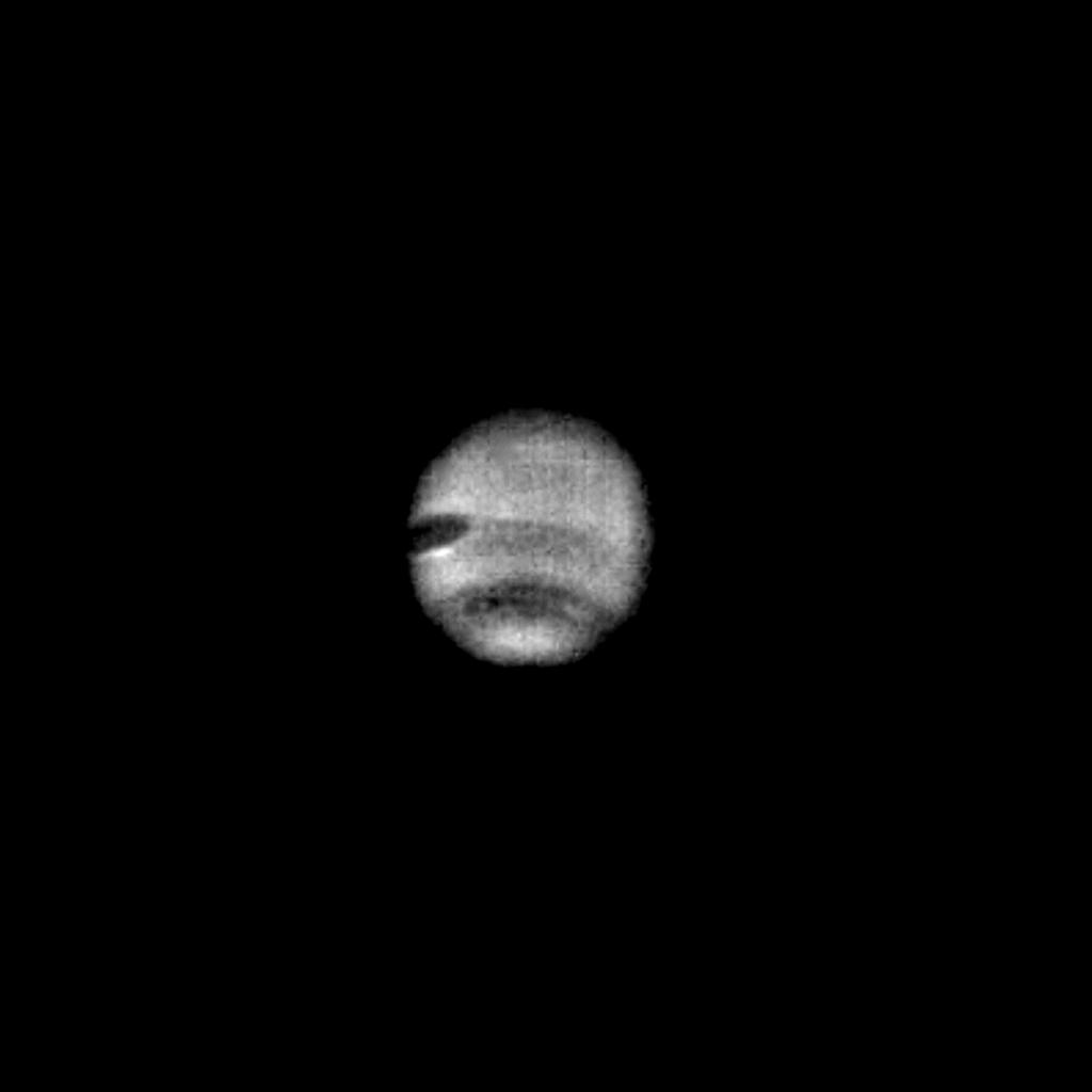 This image of Neptune was taken through the clear filter of the narrow-angle camera on July 16, 1989 by NASA's Voyager 2 spacecraft. The image was processed by computer to show the newly resolved dark oval feature embedded in the middle of the dusky south