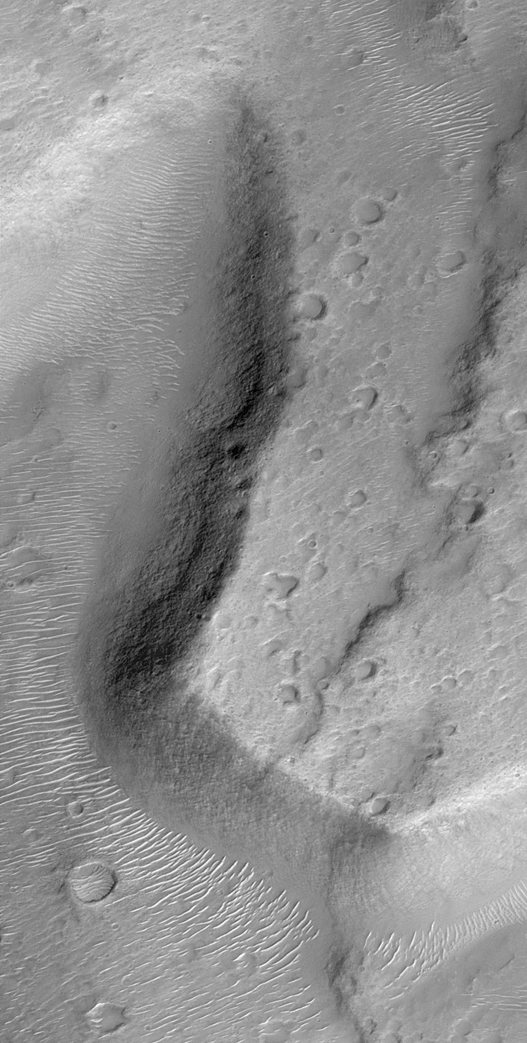NASA's Mars Global Surveyor shows escarpments and valleys on the lower northeast flank of Tyrrhenna Patera, thought to be an ancient volcano located in Hesperia Planum in the martian southern hemisphere.