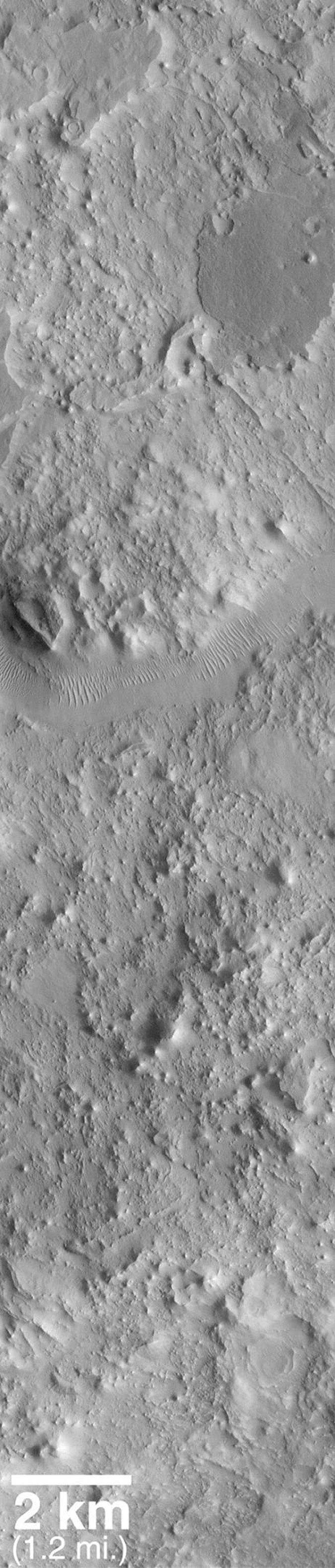 NASA's Mars Global Surveyor shows a portion of the ancient Auqakuh Vallis and many eroded remnants of the ancient cratered terrain.