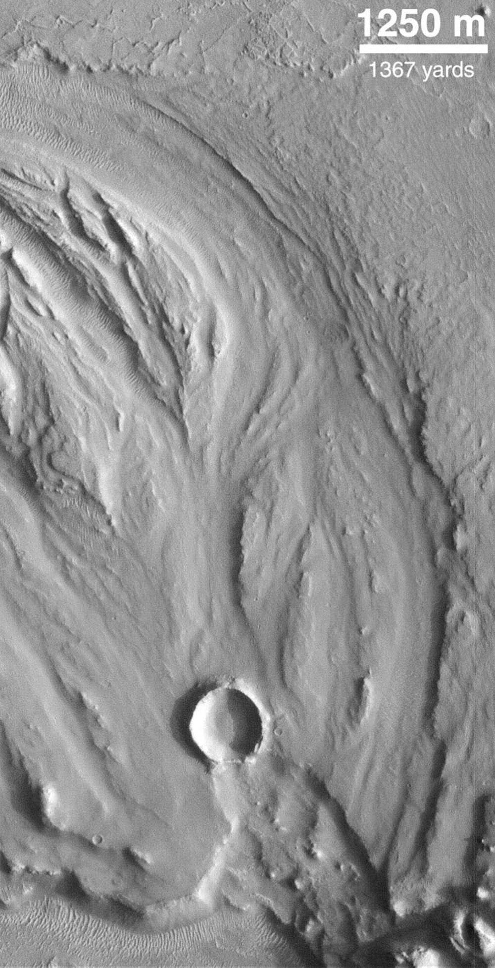 NASA's Mars Global Surveyor shows a fluid-scoured surface in the Hrad Vallis system, located northwest of Elysium Mons on Mars. The fluid is presumed to have been water.