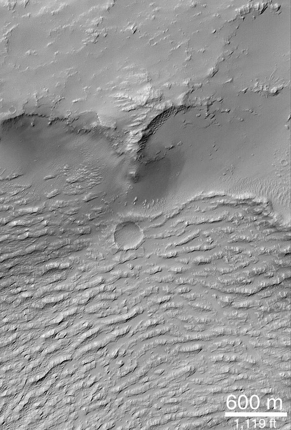 NASA's Mars Global Surveyor shows the ridged surface in the lower half of this image is that of a large lava flow in Daedalia Planum, southwest of the Arsia Mons volcano. This image was taken June 5, 1999.