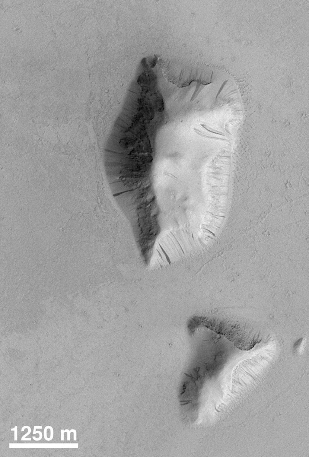 NASA's Mars Global Surveyor shows two buttes in the Elysium Basin on Mars. Exhibited are many small dark streaks on their slopes. Each streak is the result of mass-movement (landslides). Darker streaks appear to be younger than the brighter ones.