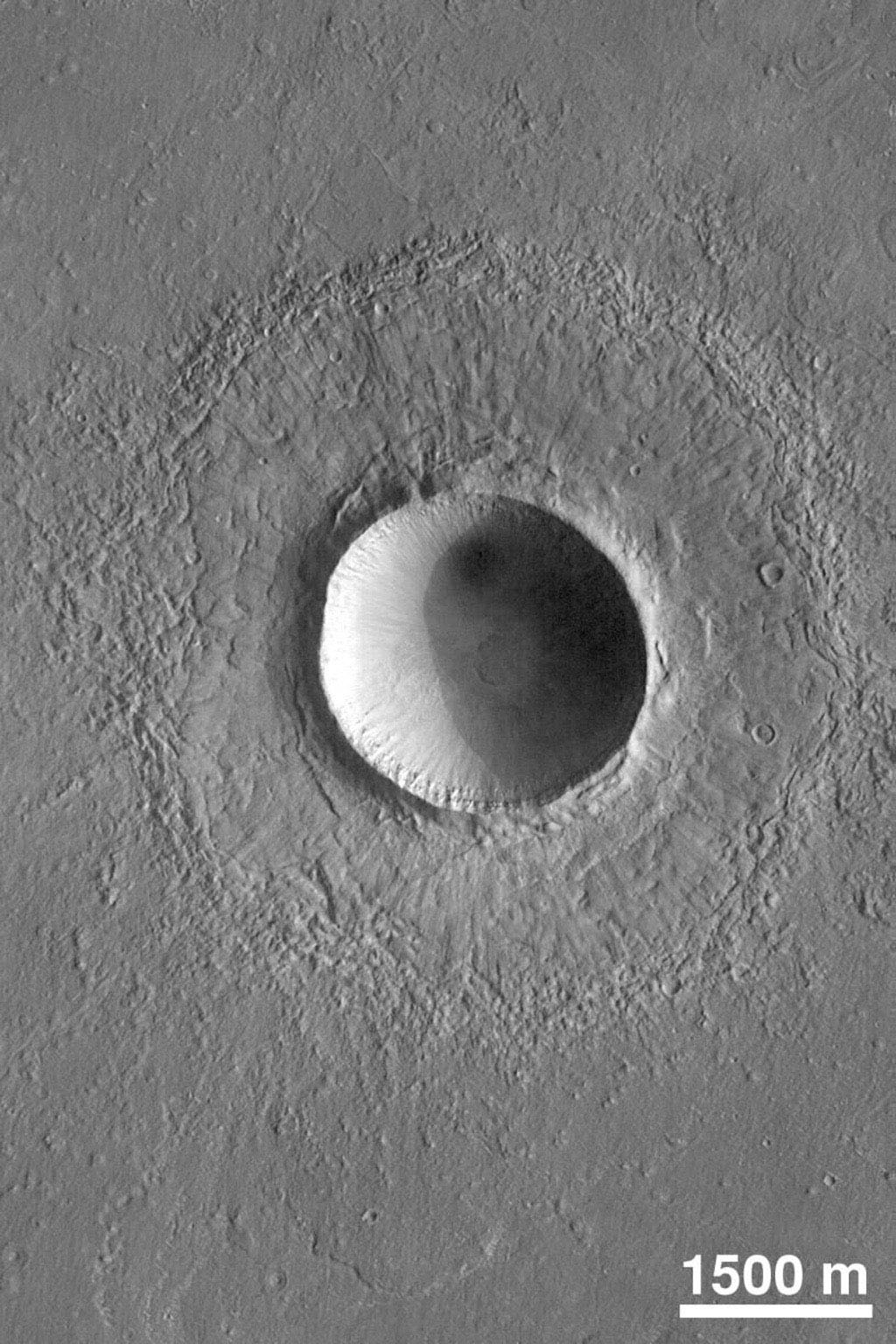 NASA's Mars Global Surveyor shows a crater on northern Elysium Planitia on Mars, a little more than twice the diameter of the famous Meteor Crater in Arizona, U.S.A. It formed by the impact and subsequent explosion of a meteorite.