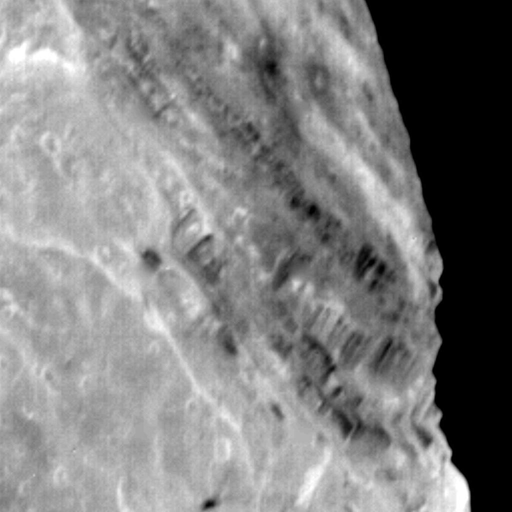 View of Miranda showing light and dark banded scarps near the boundary of the banded ovoid and a deep graben that bounds the ovoid in this region.