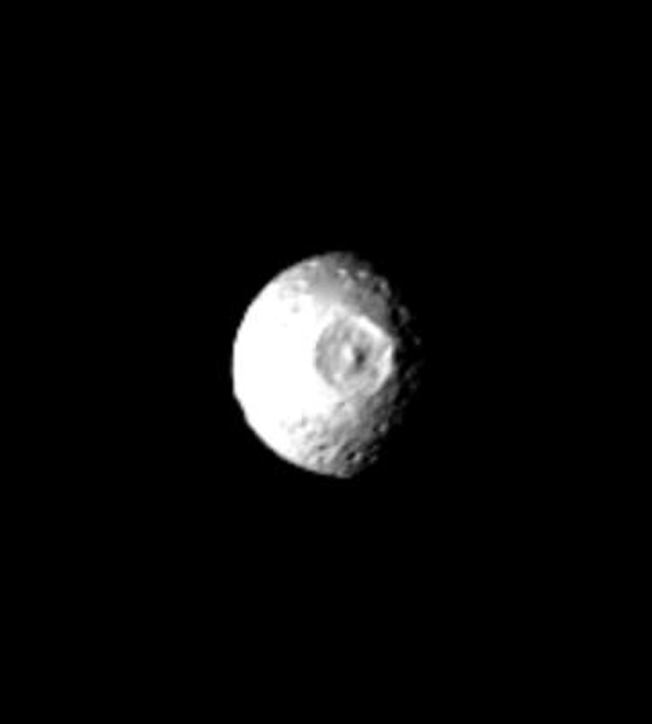 This NASA Voyager 1 picture of Mimas shows a large impact structure at 110 W Long., located on that face of the moon which leads Mimas in its orbit. The feature, about 130 kilometers in diameter, is more than one-quarter the diameter of the entire moon.