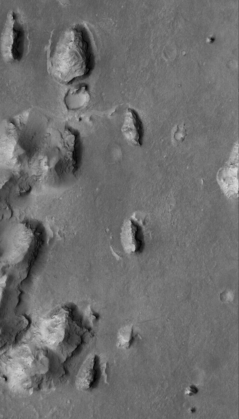 This image from NASA's Mars Global Surveyor shows layered buttes, knobs, and other landforms exposed by erosion in the Aeolis region of Mars.