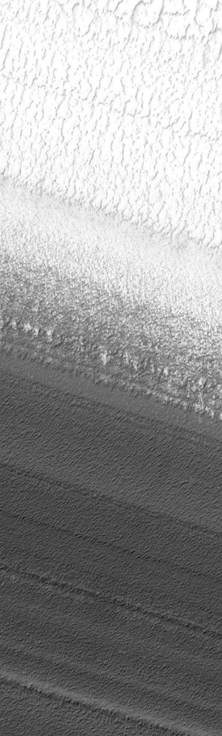 NASA's Mars Global Surveyor shows Mars' north polar residual cap surface, seen to grade downhill into exposures of layered terrain.