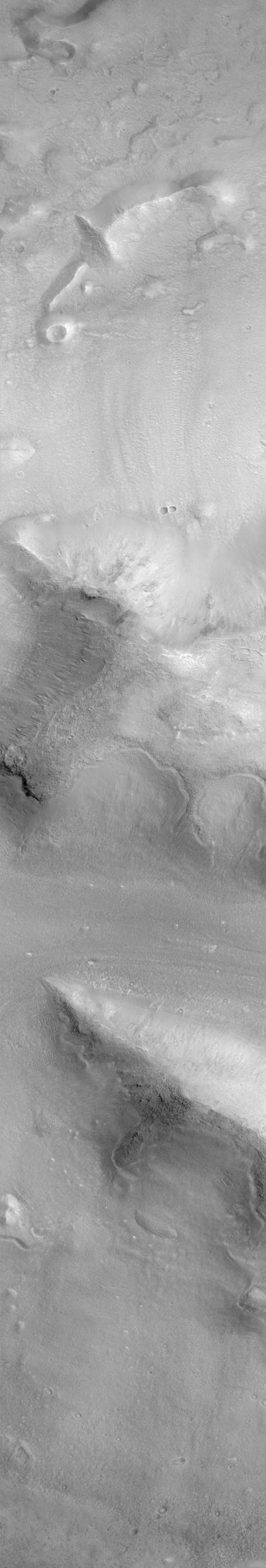NASA's Mars Global Surveyor shows a group of four small hills surrounded by the larger mountains in the Cydonia region of Mars.