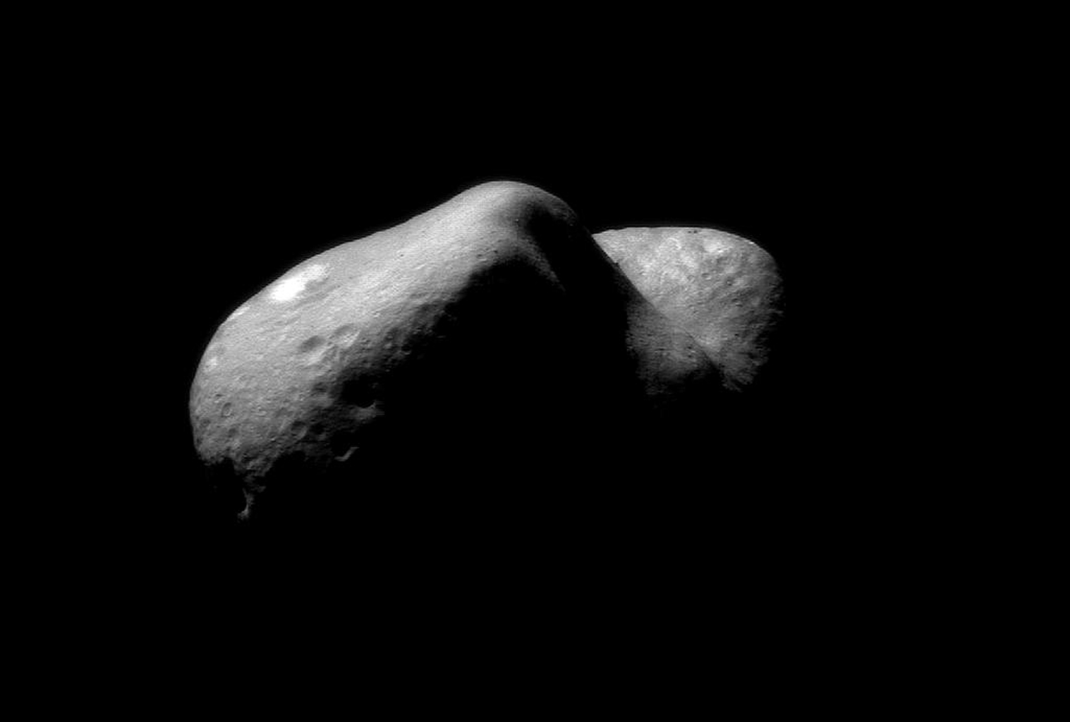 This image of Eros, taken on Feb 14, 2000 by NASA's NEAR Shoemaker spacecraft, shows the view looking from one end of the asteroid across the gouge on its underside and toward the opposite end. House-sized boulders are present in several places.