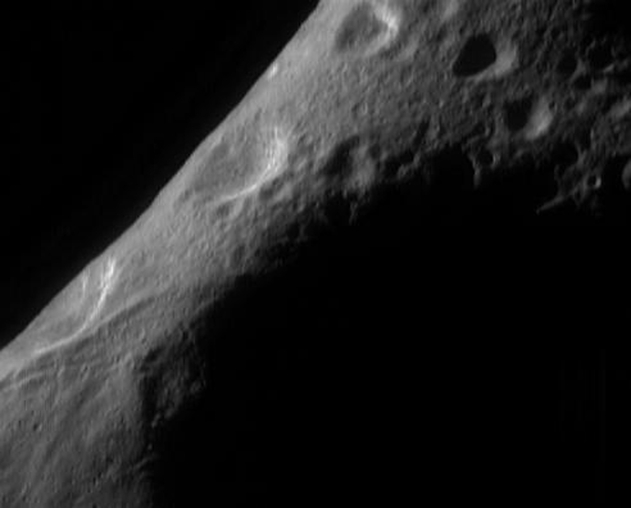 This image from NASA's NEAR Shoemaker shows the shaded interior of the 'saddle' on asteroid Eros looking over the north polar region to the limb.