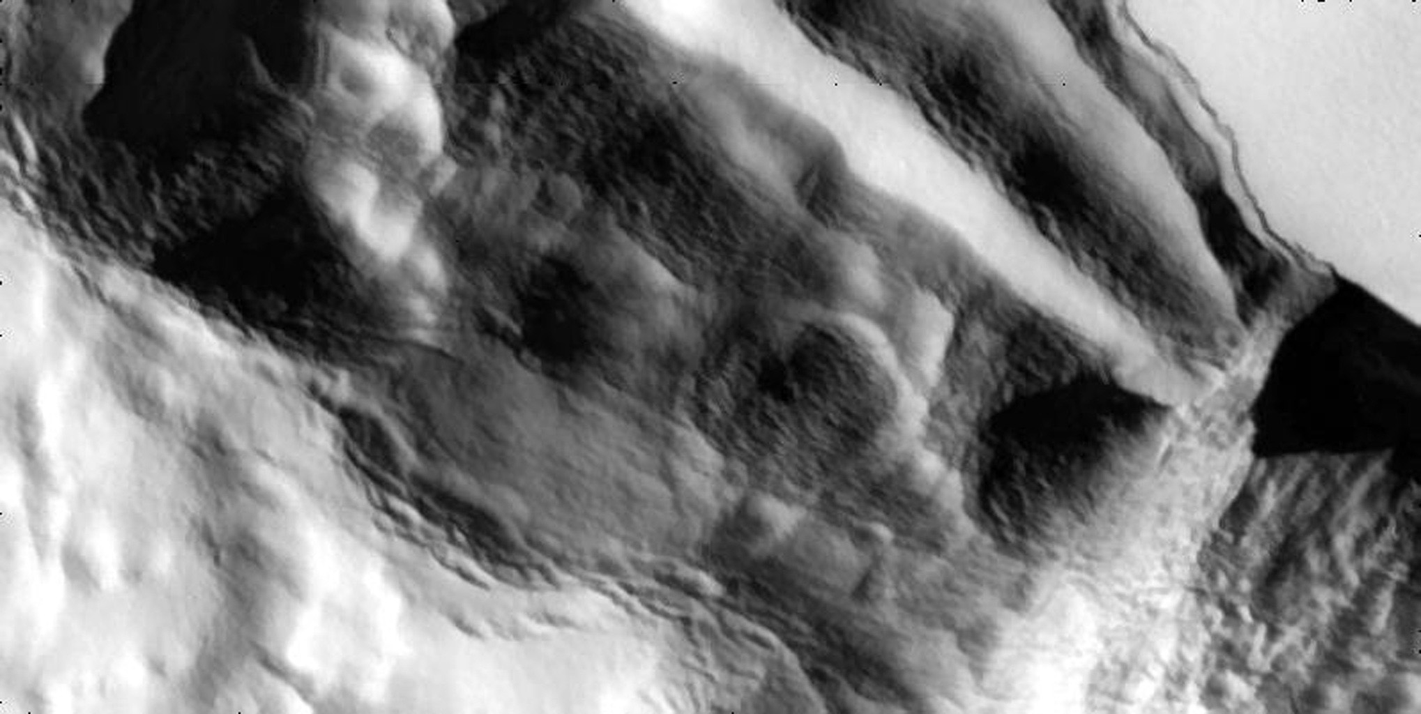 A cliff slumps outward in these high-resolution views that NASA's Galileo spacecraft captured the edge of a mountain named Telegonus Mensa on Jupiter's moon Io.