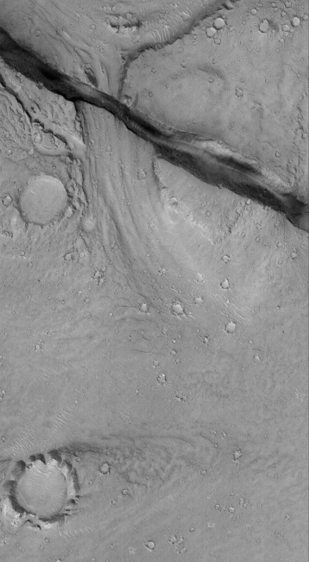 NASA's Mars Global Surveyor shows a landscape in the eastern Cerberus region on Mars scoured by catastrophic floods, and later cut by a deep, dark-walled trough. The trough is radial to the Elysium volcanic region, and formed along faults in the bedrock.