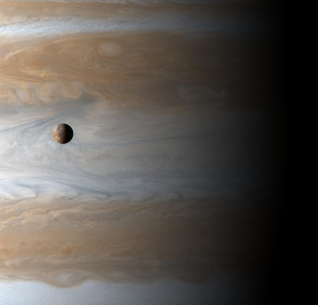 The Galilean satellite Io floats above the cloudtops of Jupiter in this image captured by NASA's Cassini orbiter on the dawn of the new millennium, January 1, 2001.
