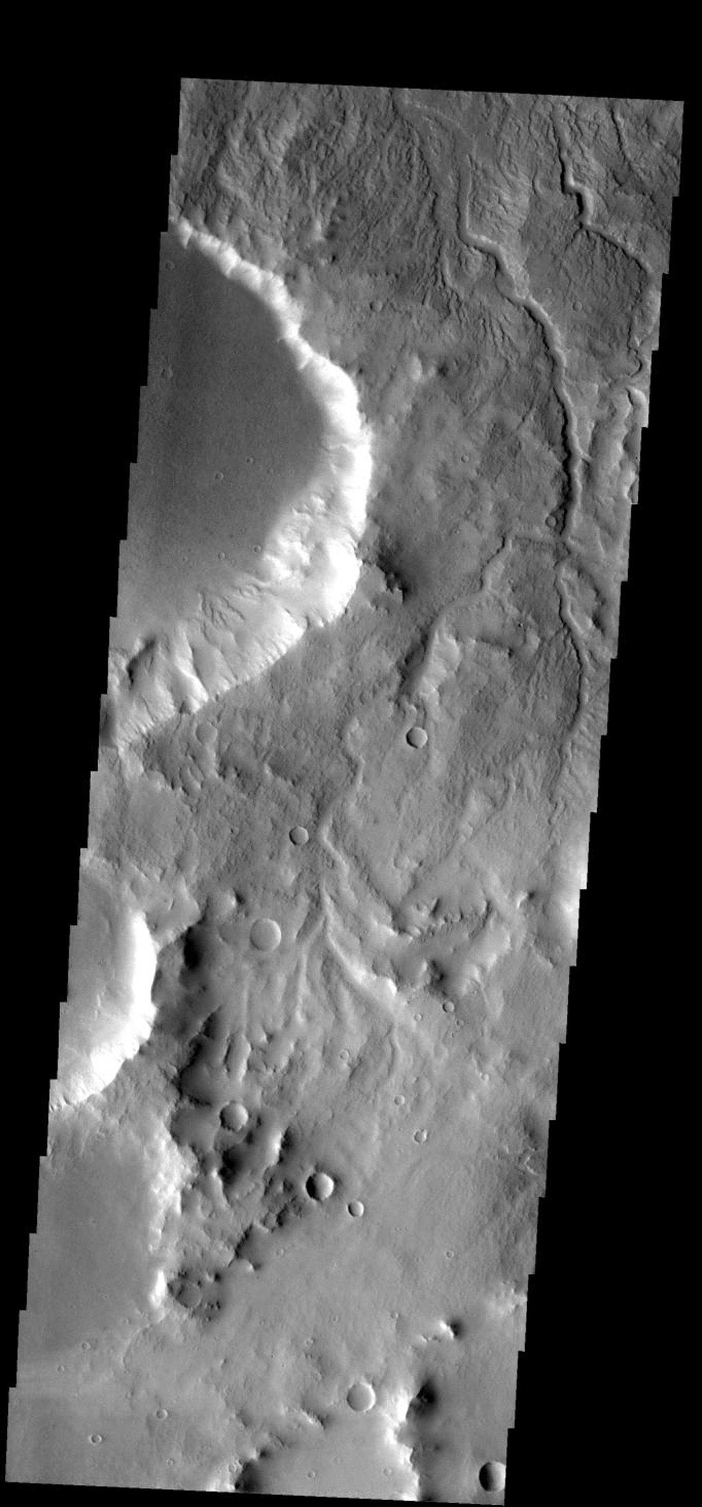 The many small channels dissecting the top part of this image are drainage valleys on Mars. Most are draining downhill to the top of the image as seen by NASA's 2001 Mars Odyssey.