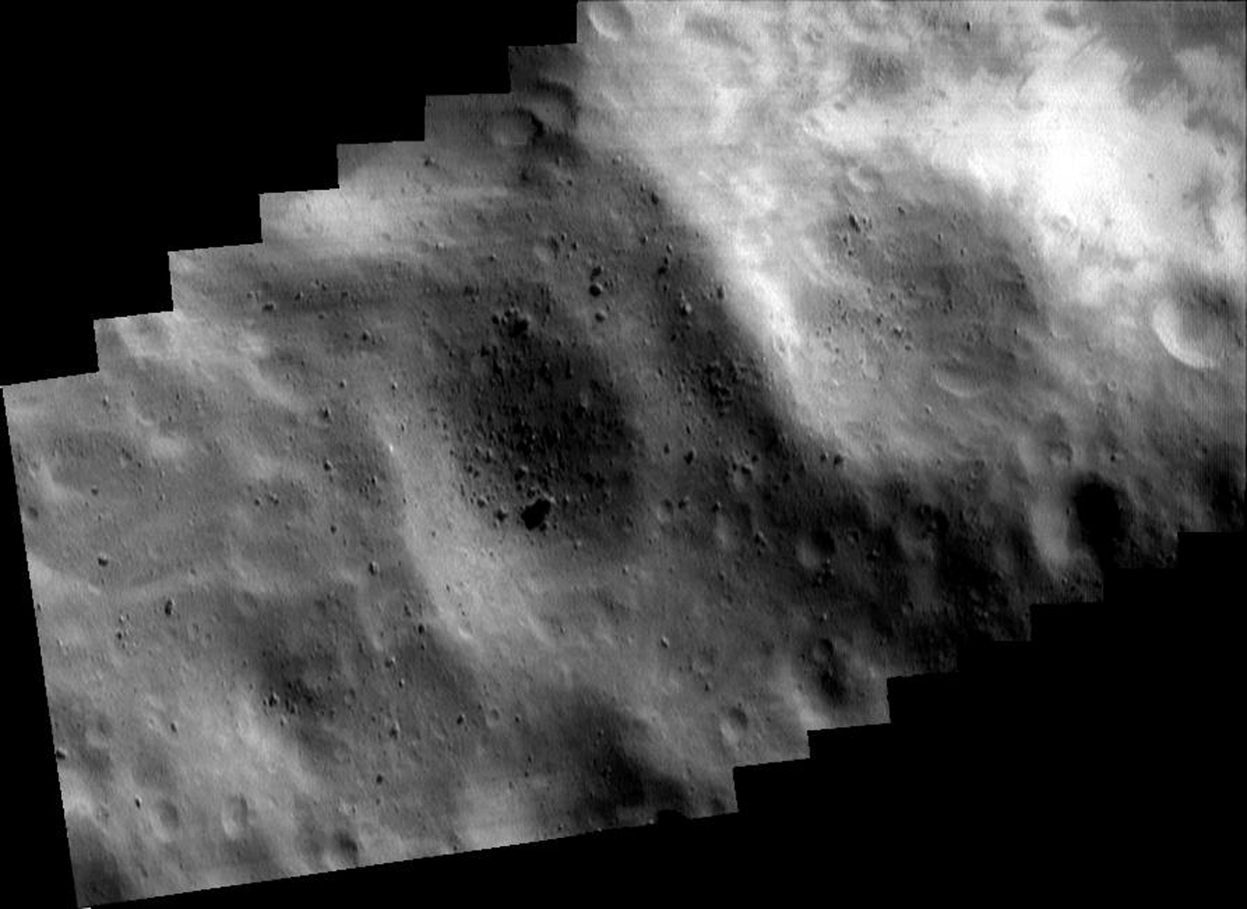This image of asteroid Eros, taken by NASA's NEAR Shoemaker on May 14, 2000, shows bright patches at upper right that are relatively freshly exposed regolith on the inside wall of the crater.