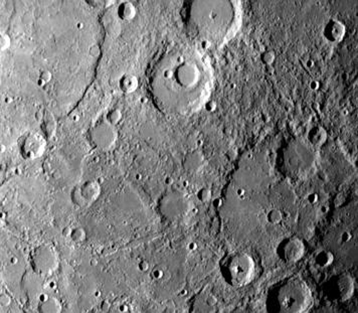 NASA's Mariner 10 photo reveals a heavily cratered terrain on Mercury with a prominent scrap extending several hundred kilometers across the upper left. A crater, nested in a larger crater, is at top center.