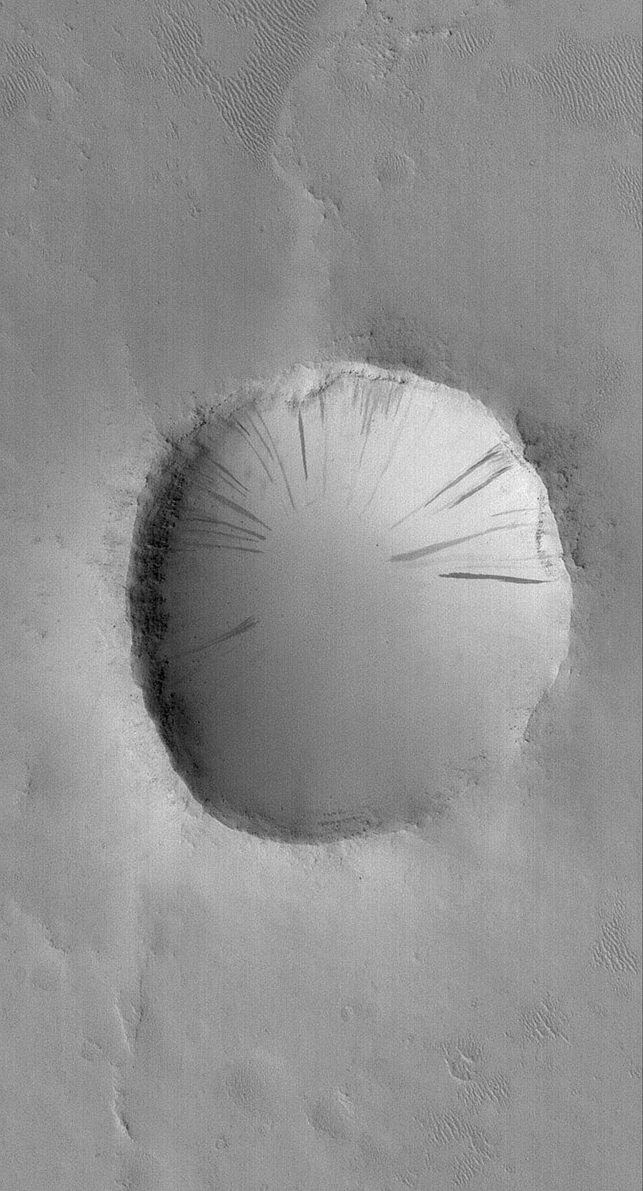 NASA's Mars Global Surveyor shows an old impact crater in southeastern Arabia Terra on Mars. The crater ejecta blanket is no longer visible and all of the terrain has been covered by a mantle of dust.