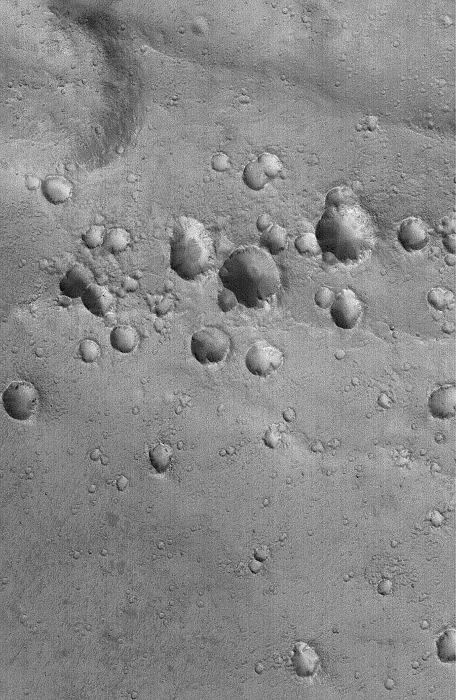 NASA's Mars Global Surveyor shows a cluster of craters in far western Arabia Terra on Mars. The crater cluster is oriented along a line that runs nearly left-right across the scene.