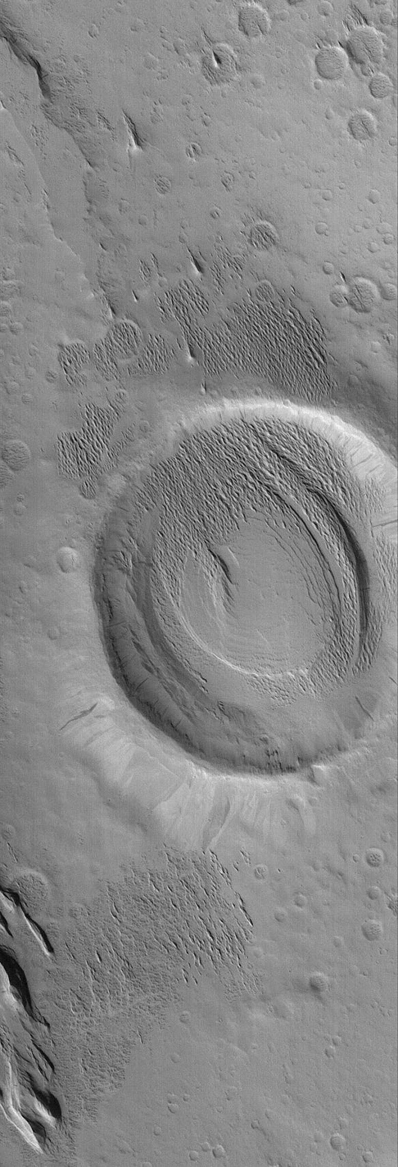 NASA's Mars Global Surveyor shows a crater and adjacent terrain that have been exhumed from beneath a wind-eroded material. The sharp, pointy ridges inside and immediately adjacent to the crater are evident.