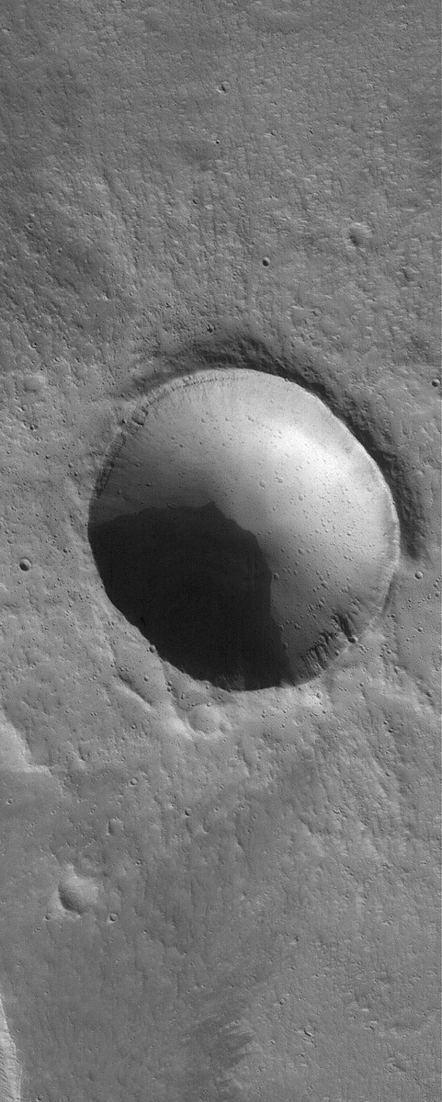 NASA's Mars Global Surveyor shows a meteor impact crater in northern Tharsis. This crater is a bit more than 2 kilometers wide, about twice the size of the famous Meteor Crater in northern Arizona, USA. Many smaller craters are evident.