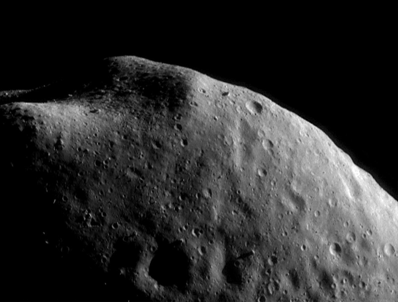 This image of asteroid Eros, taken by NASA's NEAR Shoemaker on Sept. 5, 2000, shows knobs sticking out of the surface near the top of the image surround a boulder-strewn area, robably remnants of ancient impact craters.