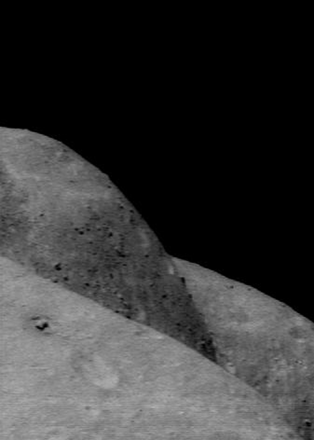 This image of asteroid Eros, taken by NASA's NEAR Shoemaker on Dec. 9, 2000, shows curvatures in the foreground and background along the eastern and western edges of the saddle.