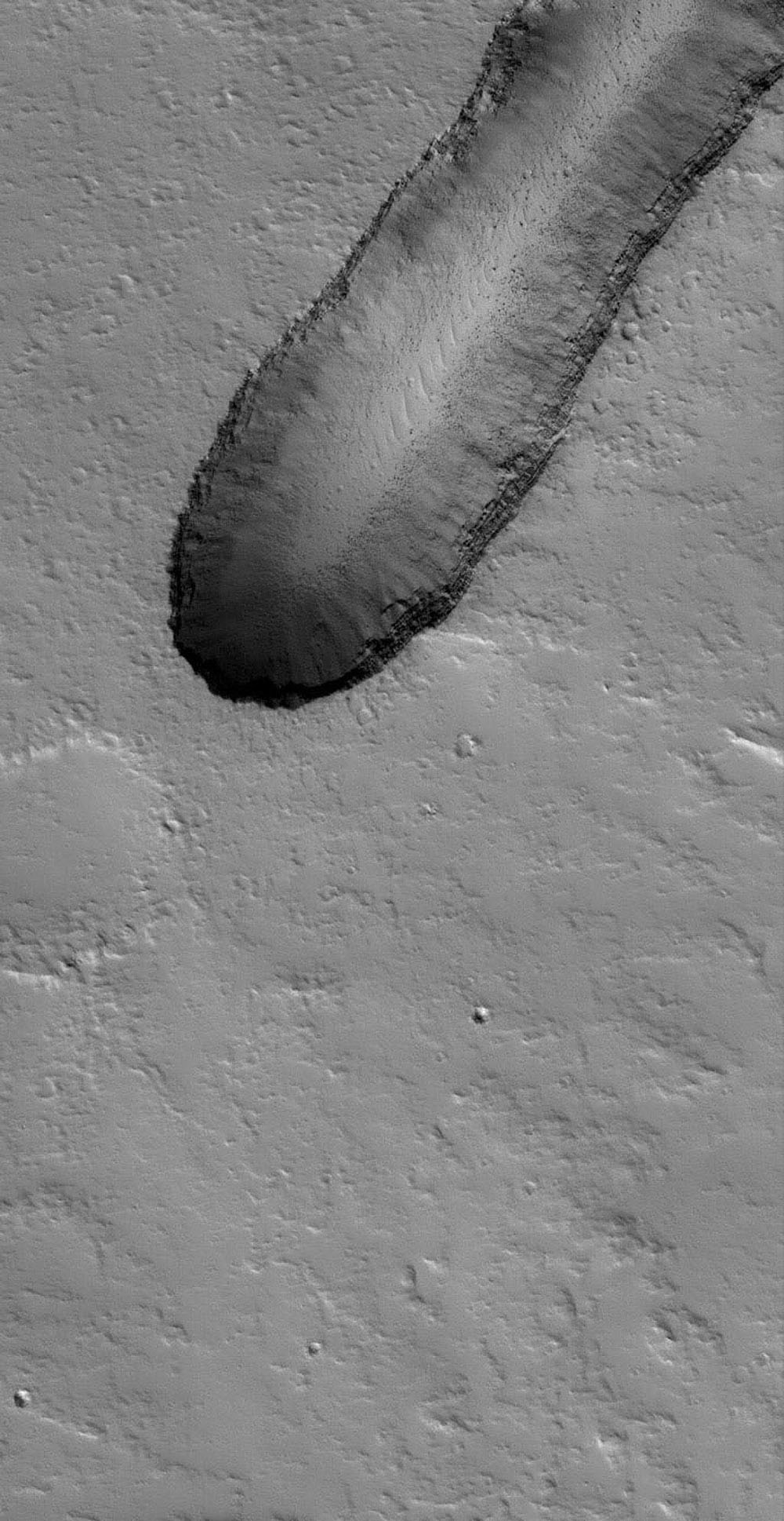 NASA's Mars Global Surveyor shows house-sized boulders and layered volcanic rock exposed in a pit on the north flank of the giant Tharsis volcano, Ascraeus Mons on Mars. The pit most likely formed by collapse.