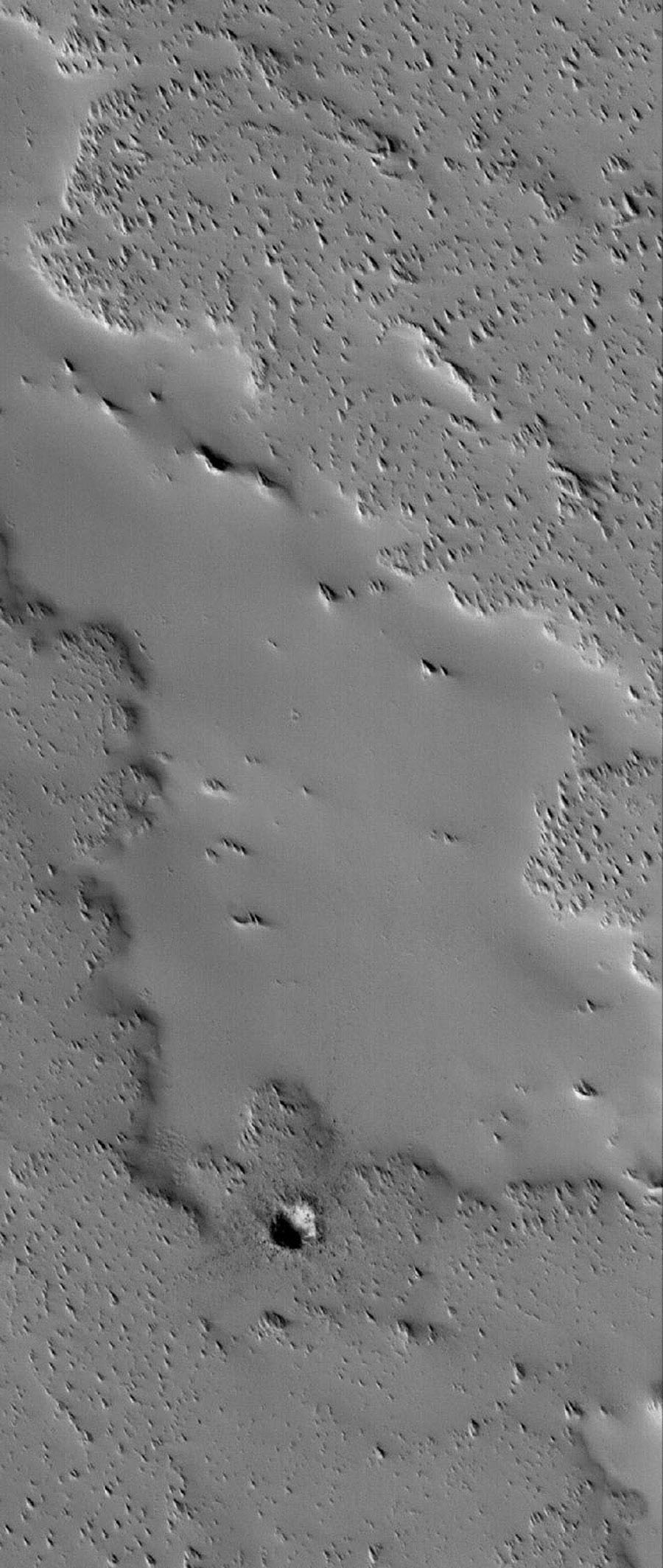 NASA's Mars Global Surveyor shows an ancient lava flow surface near the volcano, Ascraeus Mons on Mars. The volcanic material has been completely covered by thick accumulations of dust.
