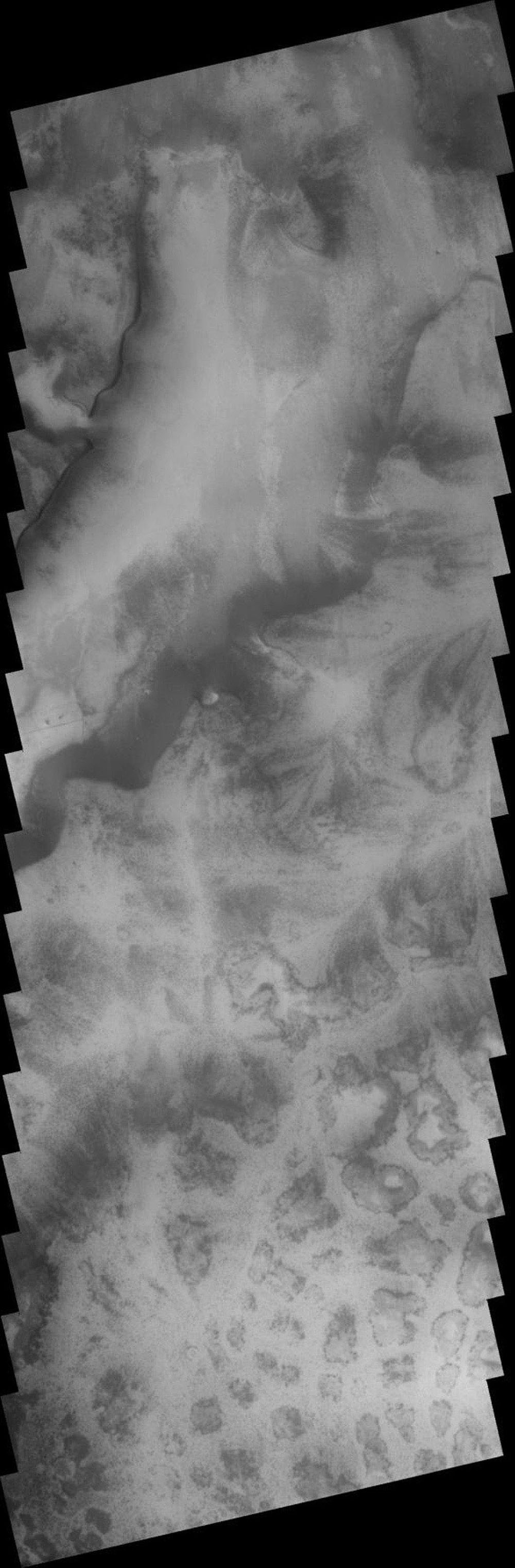 The region surrounding the south polar cap on Mars contains many different terrain types. This image from NASA's 2001 Mars Odyssey spacecraft shows both etched terrain and a region of 'mounds.'