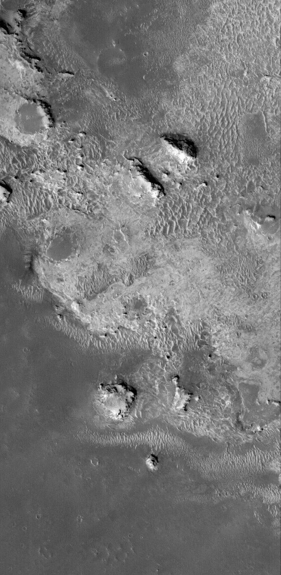 NASA's Mars Global Surveyor shows light-toned rock outcrops in northeastern Sinus Meridiani on Mars. The entire northern Sinus Meridiani region has vast exposures of light-toned, layered rock.