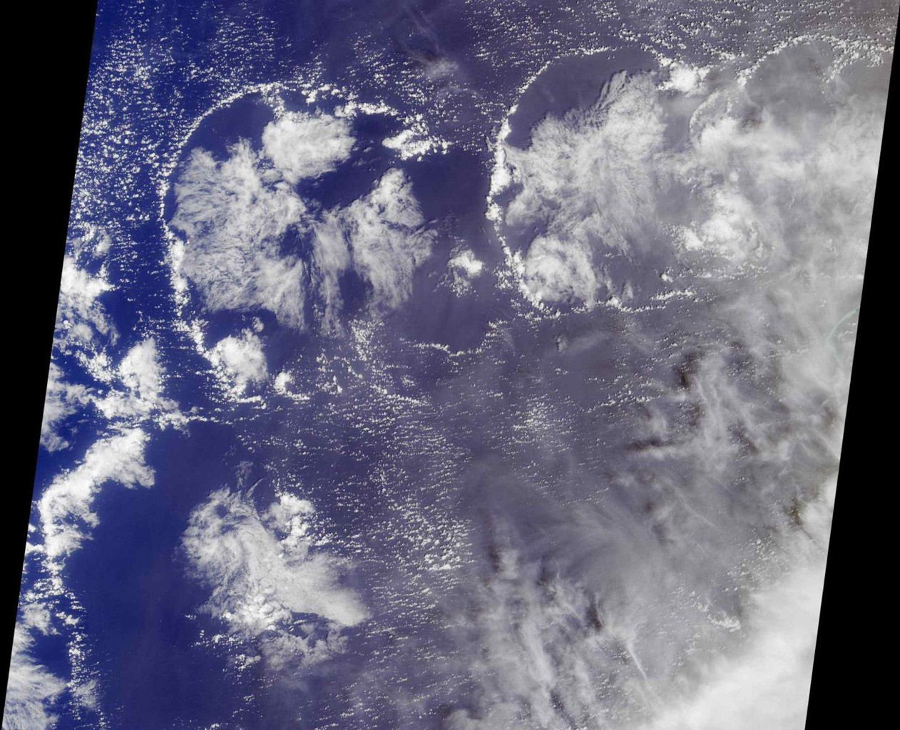 The image was acquired by NASA's Terra satellite on March 11, 2002, and is centered west of the Marshall Islands. Enewetak Atoll is discernible through thin cloud as the turquoise band near the right-hand edge of the image.
