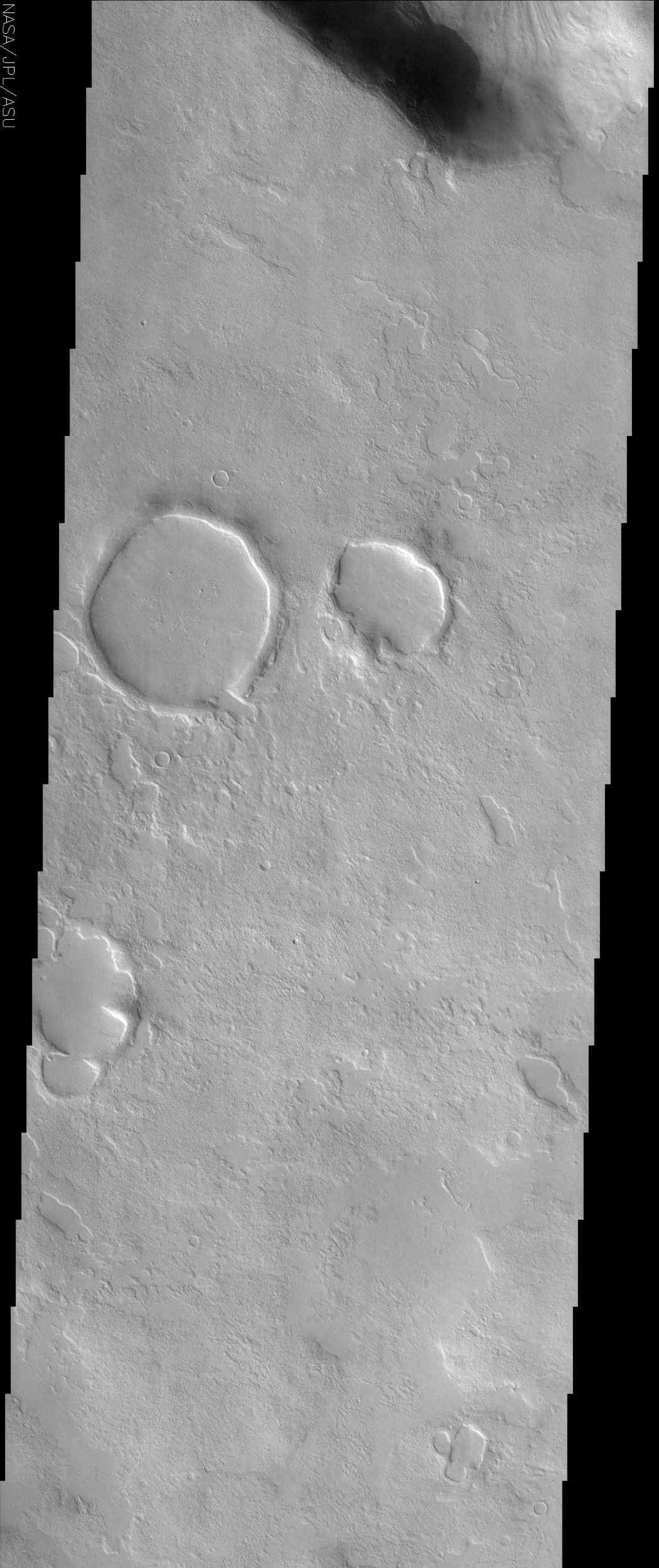 This NASA Mars Odyssey image shows a region in northern Arabia Terra where knobby or 'scabby' plains units that mantle and modify a pre-existing cratered surface dominate the unusual landscape.