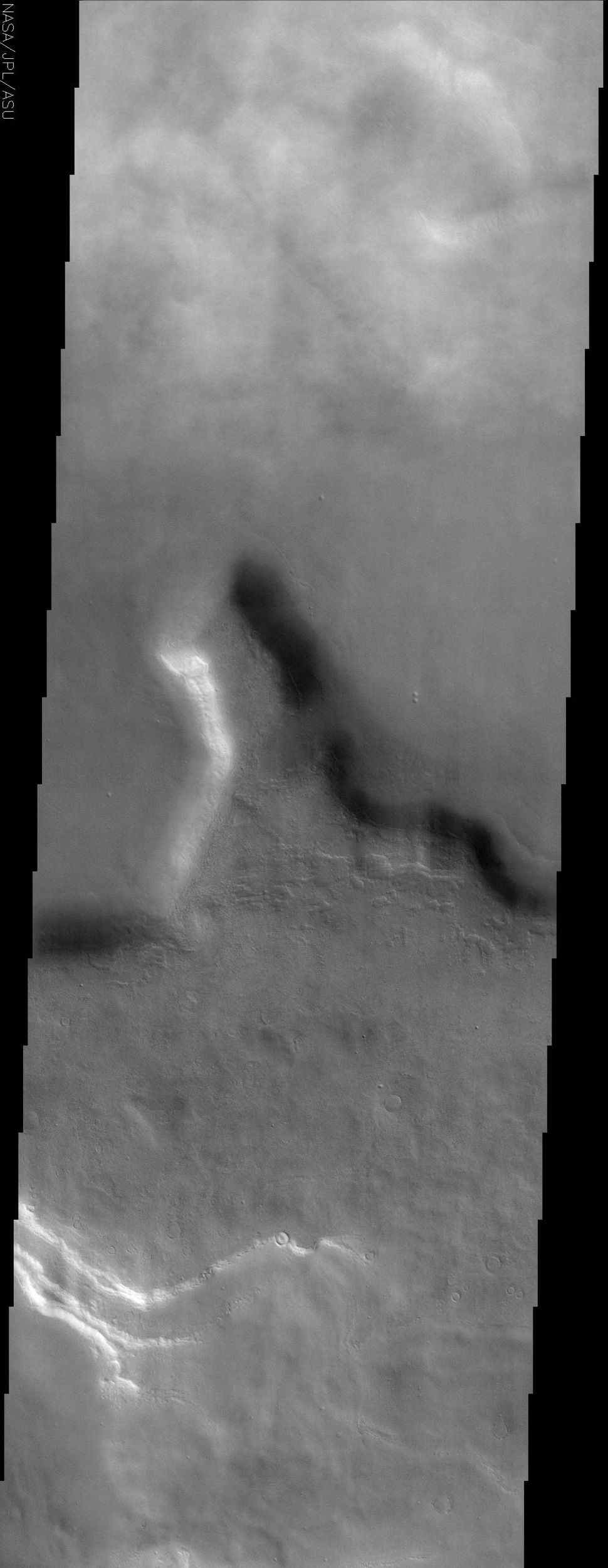 This image by NASA's Mars Odyssey spacecraft shows a region of northern Tempe Terra. Patchy water-ice clouds cover portions of the low-lying canyon at the top (north) of this image.